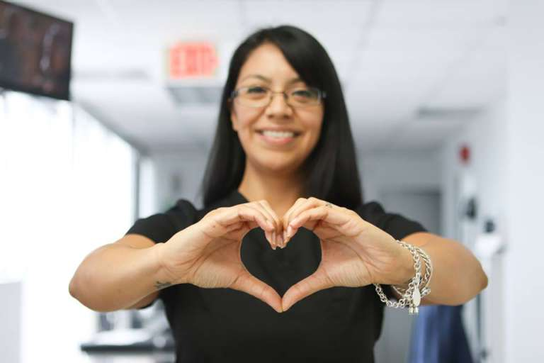 Clinic Worker holding a hand sign of a heart
