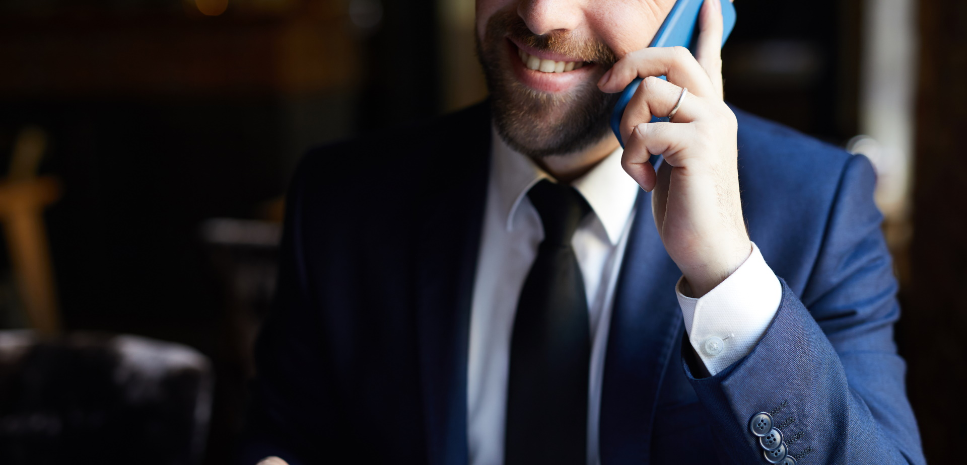Close-up of positive bearded businessman in elegant suit with coffee cup calling on mobile phone and smiling while sitting at table
